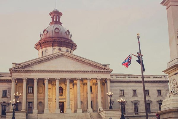 Bree Newsome removes the flag from its pole on South Carolina state Capitol grounds on June 27. (Photo by Adam Anderson)