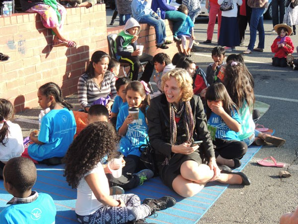 Newly elected Mayor Jennifer Roberts hangs with children outside of the ourBRIDGE offices during a Welcome Refugees event. (Photo by Ryan Pitkin)