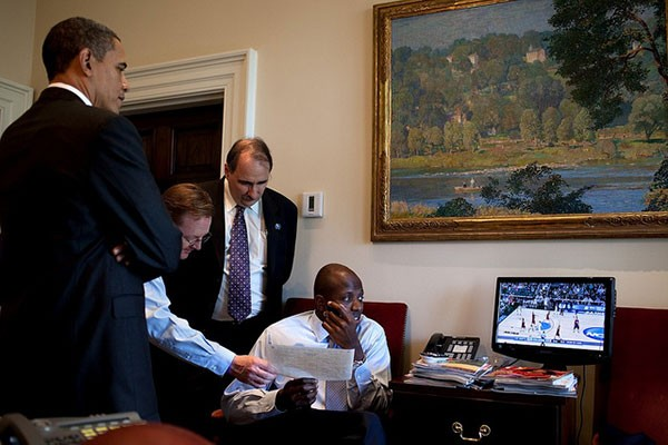 Reggie Love (right, seated) watches a March Madness basketball game in 2010 with (from left) President Obama, Press Secretary Robert Gibbs and senior advisor David Axelrod in the Outer Oval Office.