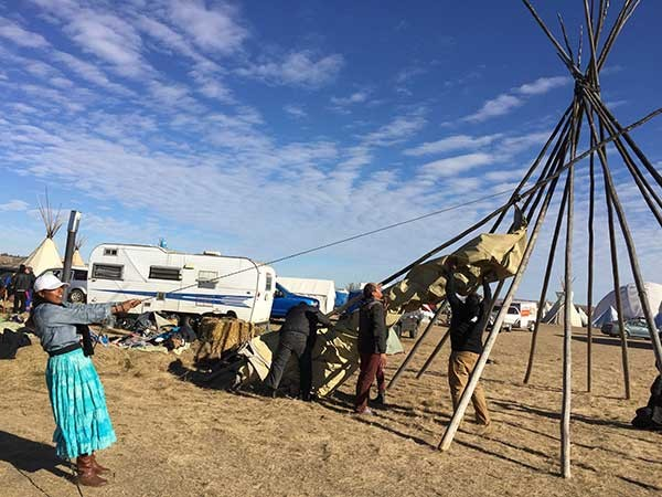 Jasmine S. LaBeau helps re-strike a teepee at the Oceti Sakowin camp on Nov. 15 in preparation for the winter.