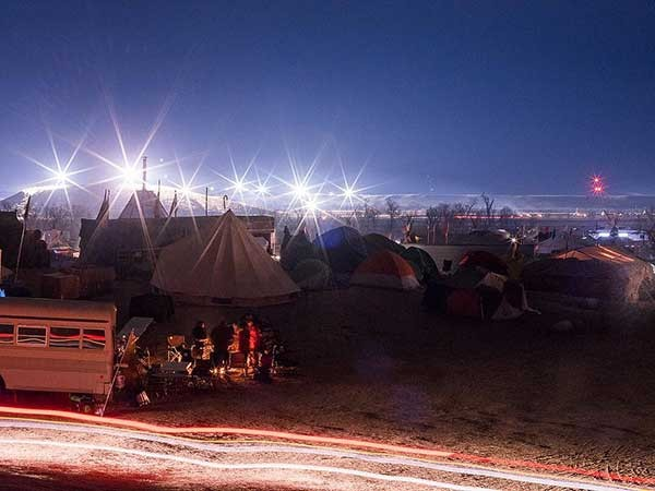 The Oceti Sakowin camp at night. The lights in the distance are the pipeline construction site. - ERIC SCHWABEL