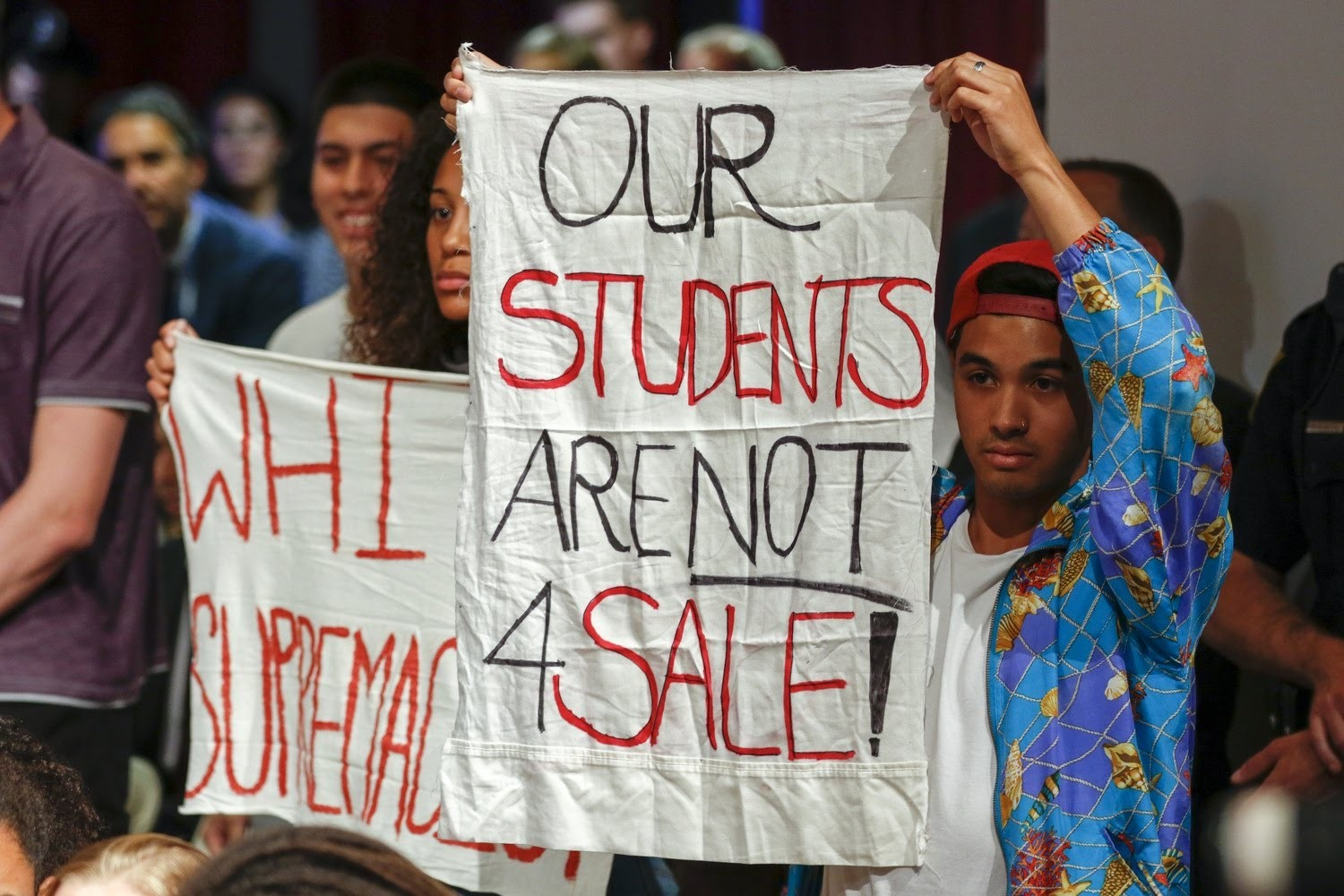 Quisol (right) holds up a sign protesting a speech by Trump's Education Secretary Betsy DeVos at Harvard in September 2017.