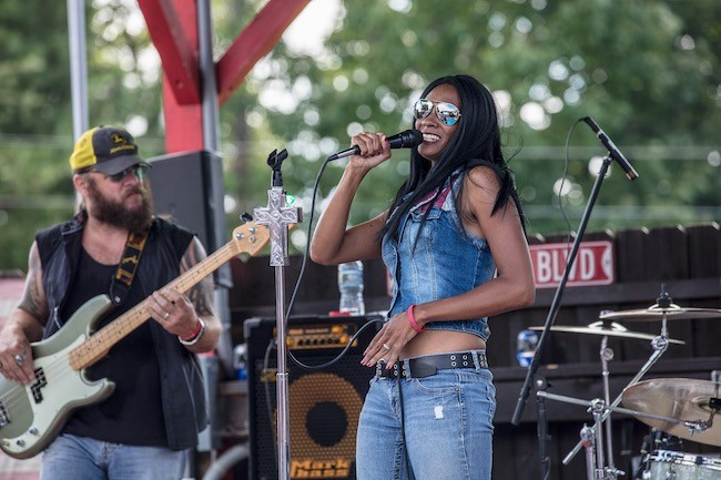 Adrienne Nixon Basco (foreground) and her bassist husband Rich Basco rock an outdoor stage with their band Tombstone Betty. (Photo by Cody Bennett)