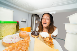 Woman looking at sweet treats in refrigerator - Uploaded by ajnewso2
