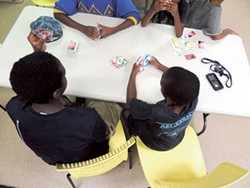 Members of the Boys and Girls Club at Salvation Army's Center of Hope play cards on a summer day. Staff members at the shelter say space is crunched during the summer.