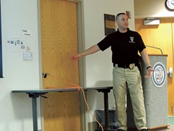 CMPD officer Christopher Kopp addresses county employees in front of an outward-opening door he barricaded using a table and extension cord at an active shooter training class on February 1. (Ryan Pitkin)