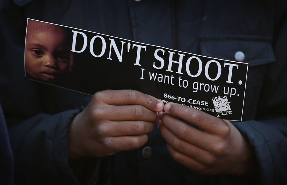 A bumper sticker held by a child during a recent peace vigil in the Washington Park neighborhood