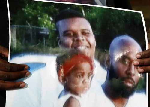 A family photo of Michael Brown (top), his father, and an unidentified child, held at a protest Monday. Some media outlets first used Browns Facebook profile photo, which critics said could have been seen in a negative light.