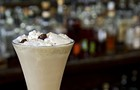 A Matchbox bartender inserts spotted dick into a creamy cocktail recipe