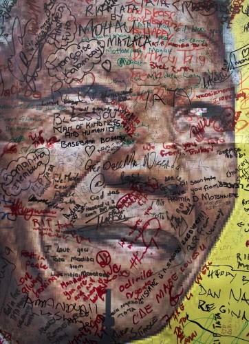 A poster of Nelson Mandela on which well-wishers have written their messages of condolence and support, in the street outside his old house in Soweto, Johannesburg, South Africa.