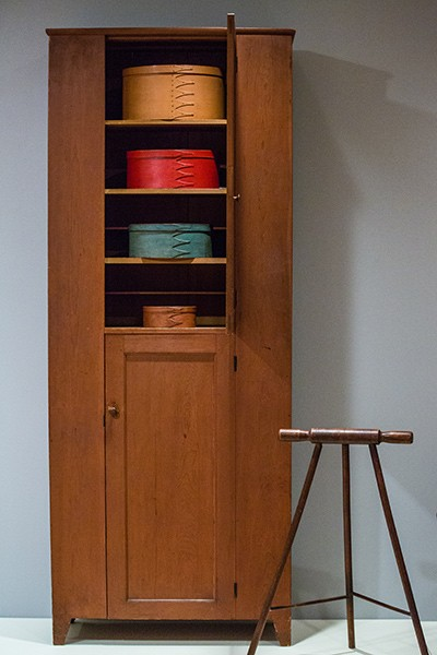 A Shaker cabinet with oval boxes.