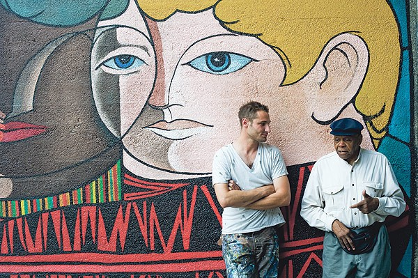 Artists Nicholas Kashian and William Walker in front of Walker's mural Childhood Without Prejudice, on the Illinois Central viaduct at 56th Street, which Kashian recently restored