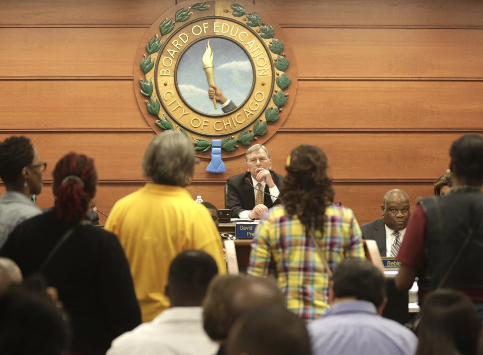 Chicago Board of Education President David Vitale, center, listens to opponents of proposed school closures at a packed board meeting Wednesday, May 22.