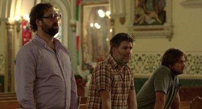 Eric Wareheim, James Murphy, and Tim Heidecker, looking apathetic in a church