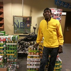 Frank Tooley, who does odd jobs at New Beginnings Church, stands in the church lobby just after the polls closed yesterday. Behind him are canned goods the church is collecting for a Thanksgiving food drive, and a motorcycle it will auction off to raise money for a community center across the street.