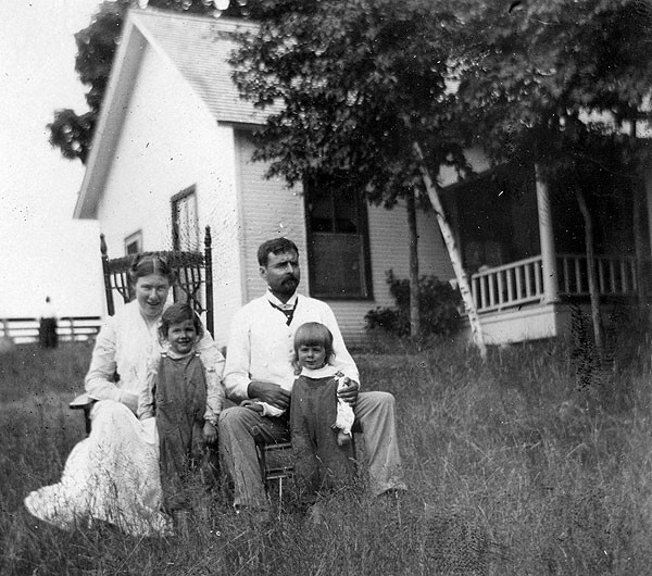 Grace, sister Marcelline, Clarence, and Ernest in front of the cottage, 1901