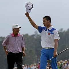 Guan Tianlang, 14, of China, acknowledges the cheers after sinking a birdie putt on the 18th green at the Masters. To his left is a playing partner today, 61-year-old Ben Crenshaw.