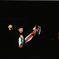 """Canadian hardcore band Single Mothers' photos from their trek through Detroit and Chicago """"I have a longstanding tradition of robbing a flagpole every time I go on a US tour. Here I celebrate my catch as I show off my tour laminate in one hand and a cheap 40-ounce in the other."""" Leor Galil"""