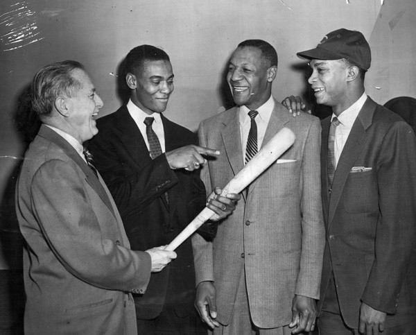 In 1955, the Cubs made former Negro League manager Buck O'Neil their first black scout. Shown at the announcement, from left: personnel director Wid Matthews; shortstop Ernie Banks; O'Neil; second baseman Gene Baker. - SUN-TIMES PRINT COLLECTION