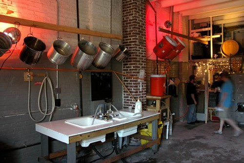 Inside the CHAOS brew house: Brew kettles at left, mash tuns at right. Most of the mash tuns are being used outside as water coolers.