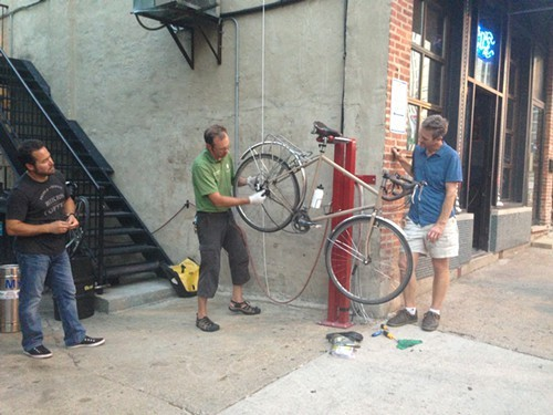 Jason Jenkins demonstrates how to change a tire at the Paramount Rooms new bike fix-it station