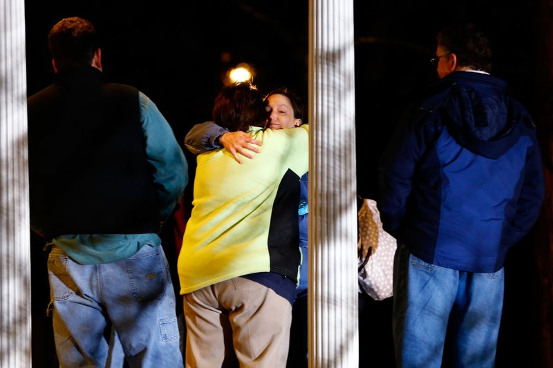 People hug outside of the Newtown United Methodist Church.