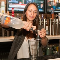 Monica Dim makes the Professor Plum Pour two ounces of Grey Goose L'Orange into a mixing glass. Andrea Bauer