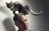 A photo of Morrissey with a cat on his head