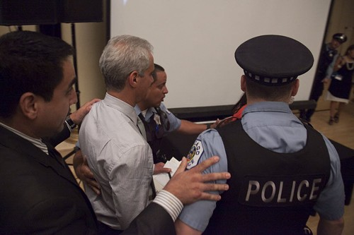 Police  escorted Emanuel out of a budget hearing last night after protesters took over the stage. - ASHLEE REZIN/SUN-TIMES MEDIA