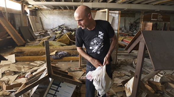 With permission from the city of Gary, Chicago artist Jan Tichy rummages through an abandoned tile and carpet store. - RUTH LOPEZ