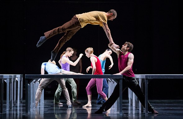 Kevin J. Shannon bearing Jesse Bechard in One Flat Thing, Reproduced; upstage from left are Florian Lochner, Alice Klock, David Schultz, Emilie Leriche, and Ana Lopez - TODD ROSENBERG