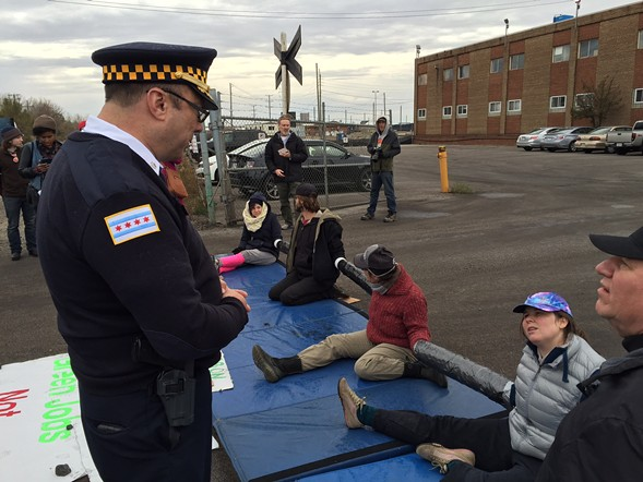 Fourth District police commander Kevin Navarro talks with protesters blocking the entrance to KCBX Terminals' south site. - ROBIN AMER