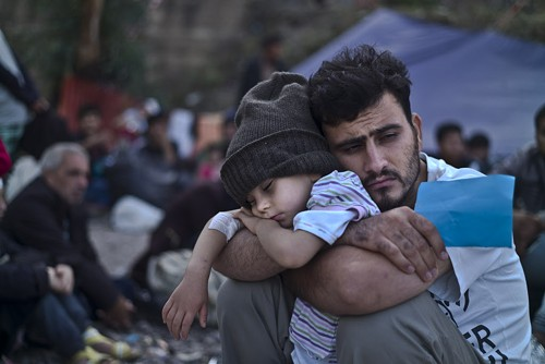 A father and child, Syrian refugees, waiting to board a bus on the northeastern Greek island of Lesbos. - AP PHOTO/MUHAMMED MUHEISEN