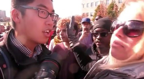 "Janna Basler, right, who works in the University of Missouri's office of Greek life, tells photographer Tim Tai, to ""leave these students alone"" in their ""personal space."" - MARK SCHIERBECKER VIA AP"