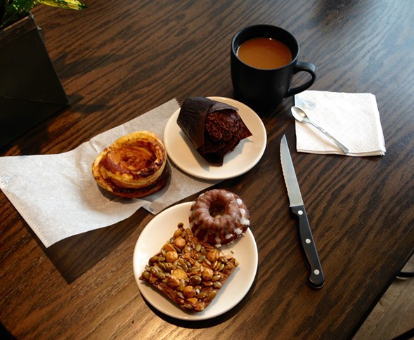 Coffee and pastry at Loba (clockwise from left): ham and cheese kouign amann, chocolate cardamom muffin, Robbie, pepita crunch bar. - AIMEE LEVITT