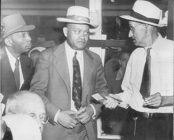 In this 1944 photo, A.T Walden (center), then-president of the Atlanta chapter of the NAACP, listens silently as an election official returns his ballot and explains he cannot vote in Georgia's democratic primary. - SUN-TIMES FILE PHOTO