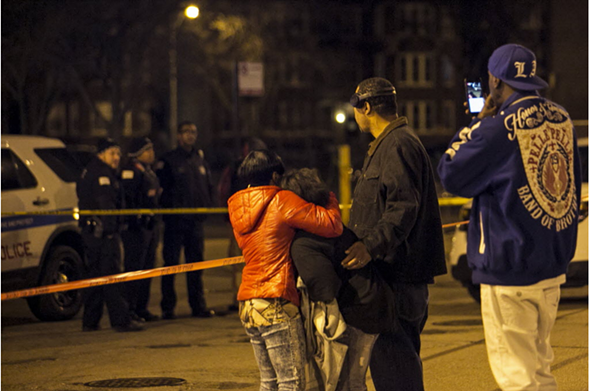 Family members and friends watch as police investigate at the scene where a 31-year-old man was shot to death in the South Shore neighborhood in March. - ASHLEE REZIN/CHICAGO SUN-TIMES VIA AP