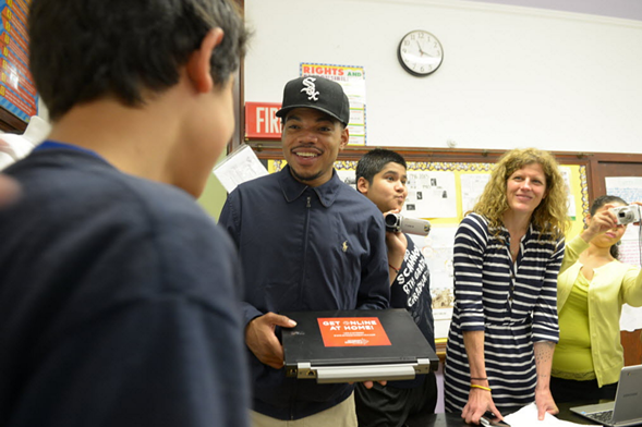 """Chance the Rapper presents awards to Scammon Elementary for winning the """"Get Schooled, Get Connected"""" educational challenge in 2015. - BRIAN JACKSON/SUN-TIMES"""