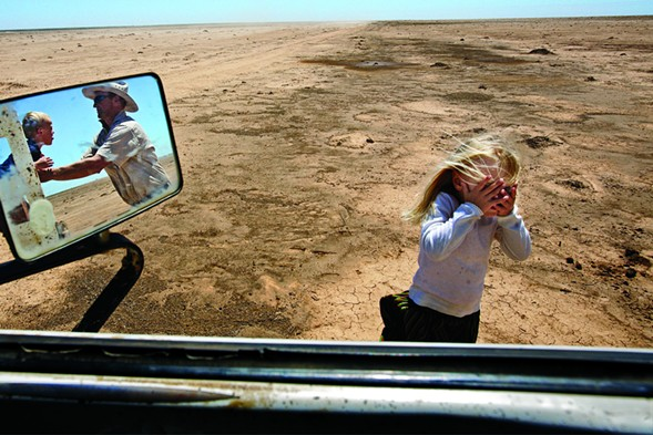 A farmer and his children play in a water-starved field in Australia where his livestock once grazed. - AMY TOENSING/NATIONAL GEOGRAPHIC