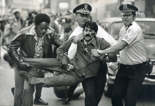 A demonstrator is arrested in front of the Medinah Temple on June 14, 1977, while anti-gay crusader Anita Bryant gives at a concert inside. - JOHN H. WHITE/CHICAGO SUN-TIMES