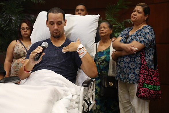 Orlando shooting survivor Angel Santiago points to the spot where his friend was shot in the chest as he speaks to the media from a Florida hospital Tuesday. - JOE RAEDLE/GETTY IMAGES