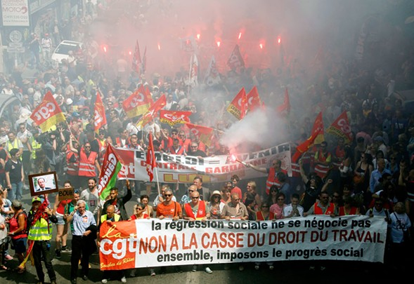 """French protesters hold a banner reading """"You do not negotiate social setbacks, let's impose social progress together. No to scrapping labor law"""" during Tuesday's march. - AP"""