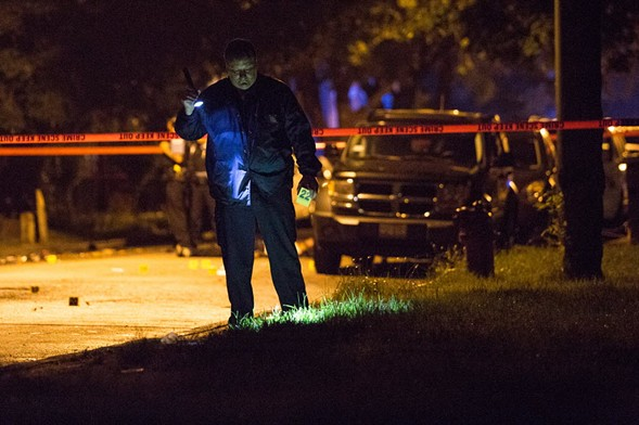 An evidence technician with the Chicago Police Department investigates the scene of a homicide in July. - LOU FOGLIA/SUN-TIMES