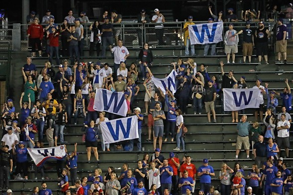 """Fans in the bleachers hold """"W"""" flags after a Cubs victory. - JONATHAN DANIEL/GETTY IMAGES"""