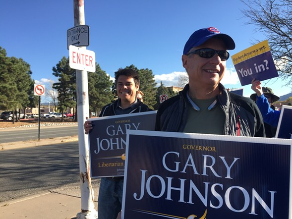 Libertarian Party presidential nominee Gary Johnson joins sign-waving supporters in Santa Fe, New Mexico, Tuesday. - AP PHOTO/MORGAN LEE