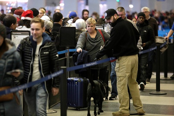A Homeland Security agent and police dog vet travelers in line at O'Hare - PHOTO BY JOSHUA LOTT/GETTY IMAGES