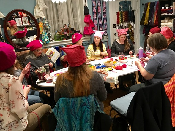 Sister Arts friends and customers knit pussyhats at the 'Marcher Send-Off Party.' - JACK LADD