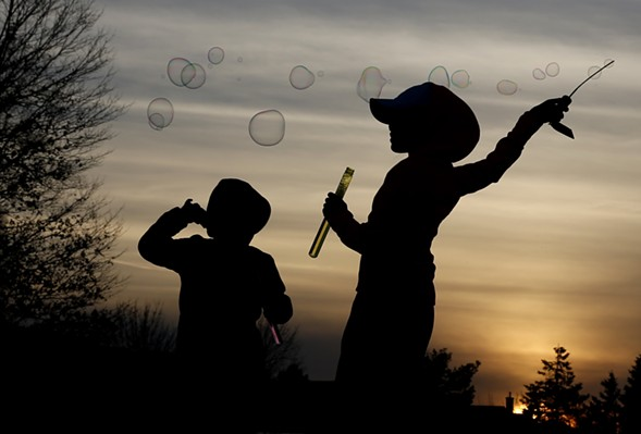 Children make soap bubbles at sunset. The springlike weather in the region broke record high temperatures this week. - AP PHOTO/NAM Y. HUH