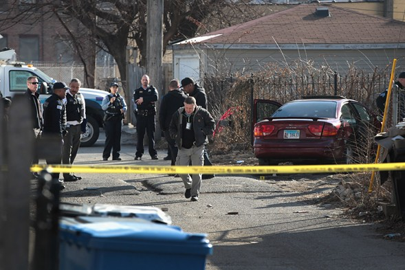 Police look over a bullet-riddled car after a gunman opened fire in Lawndale February 14, killing a two-year-old child and a man in his 20s and wounding a pregnant woman. - PHOTO BY SCOTT OLSON/GETTY IMAGES