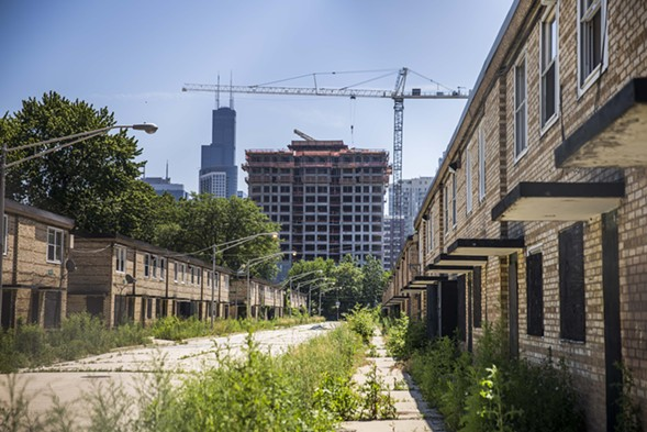 The remaining rowhouses of the Cabrini-Green public housing development stand empty as a new upscale apartment building is erected nearby. - RICH HEIN/SUN-TIMES